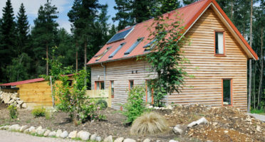 A wooden house with solar panels and a garden providing inspiration and ideas for An Camas Mòr